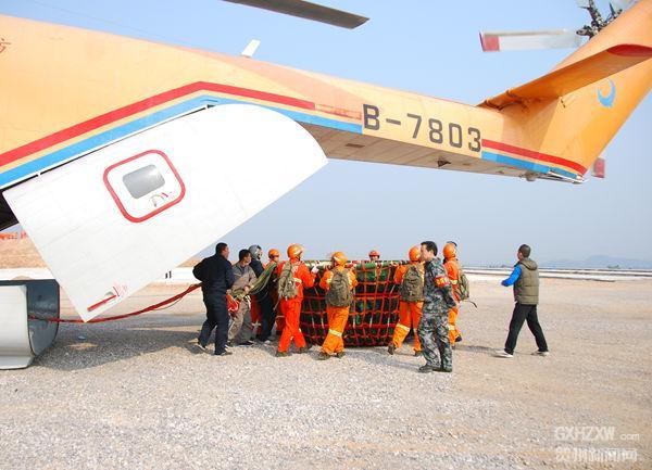 12月6日上午,我市在莲塘镇古柏村举行森林防火地空实地灭火演练。  来自各县区(管理区)、国营林场、乡镇的13支消防队伍共300多人参加了此次实战演练。  指挥长在现场进行灭火安排部署。  此次森林防火实地灭火演练调用了世界第一大和第一重直升机米-26进行灭火。  灭火指挥员在飞机上向地面发散消防知识传单。  大火熊熊燃起,消防队员立刻带上风力灭火器进入火灾现场进行灭火。  米-26直升机从火场上空撒下10多吨水,迅速压制大火。  图为消防队员们从飞机尾部取出在灭火时用于装水的吊桶。 贺州新闻网讯 为全